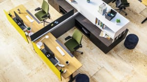 Top view of 2 workstations next to each other, divided by black and yellow screens fro privacy, with wooden desks, a green Gesture chair and dark brown Universal Storage at the back of their desks.