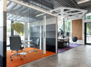 An Orangebox Air pod is seen in an office setting next to a lounge with three desk chairs arranged around a table Isolated Image